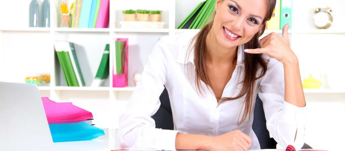 Young pretty business woman with phone and notebook working at office. Contact us